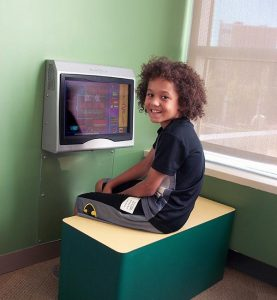Child plays a Kidzpace interactive video game to relax while waiting to see the doctor